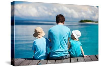 Back View of Father and Kids Sitting on Wooden Dock Looking to Ocean