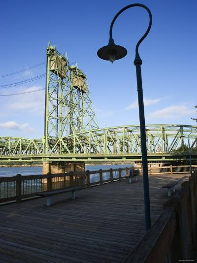 Boardwalk Along River with Industrial Bridge in the Background in Portland, Oregon--Photographic Print