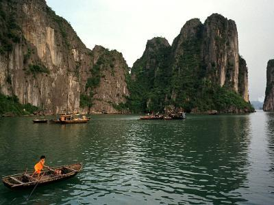 Boats Move Among the Craggy Islands of Halong Bay--Photographic Print