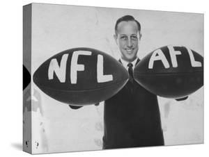 National Football League Commissioner Pete Rozelle Holding Together 2 Footballs Labeled NFL and Afl by Bob Gomel