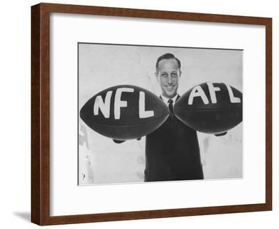 National Football League Commissioner Pete Rozelle Holding Together 2 Footballs Labeled NFL and Afl