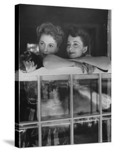 Actress Joan Fontaine with Actress Sister Olivia de Havilland Looking Out of Open Window at Home by Bob Landry