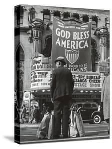 Man with Shopping Bags in Front of Million Dollar Theatre Emblazoned with God Bless America Banner by Bob Landry