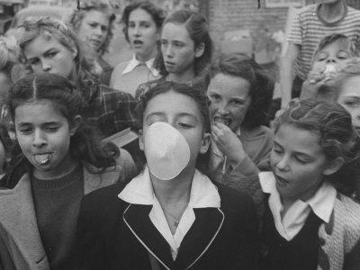 Young Girl Blowing a Bubble with Her Friends Watching