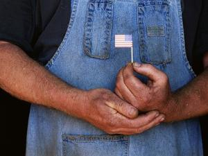 Man Holding Small American Flag by Bob Rowan