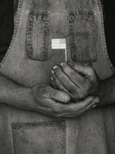 Man Holding Small American Flag by Bob Rowan