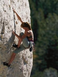 A Female Climber Searches for a Hold by Bobby Model