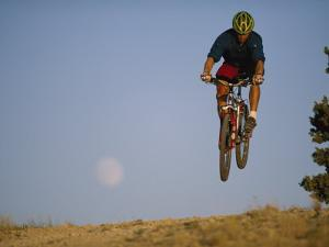 A Man Catches Some Air on His Mountain Bike by Bobby Model