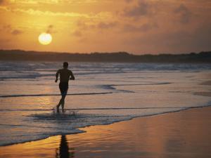 A Man Runs Through the Surf on Shella Beach at Sunset by Bobby Model
