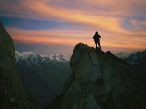 A Silhouetted Climber Watches the Sun Set over the Karakoram Mountains by Bobby Model