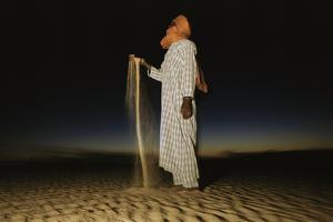 A Tuareg tribesman prays at twilight. by Bobby Model