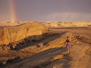 Woman Trail Running in a Rocky Landscape with a Rainbow by Bobby Model