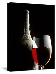 Glass of Red Wine with Aged Bottle, Cobwebs by Bodo A^ Schieren