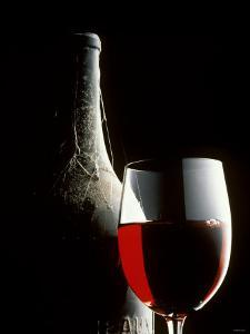 Glass of Red Wine with Aged Bottle, Cobwebs by Bodo A. Schieren