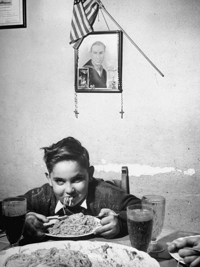 Boy Eating Spaghetti under Picture of His Brother Who Died During Invasion of Sicily--Photographic Print