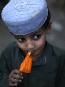 Boy Eats an Ice Lolly in a Neighborhood on the Outskirts of Islamabad, Pakistan
