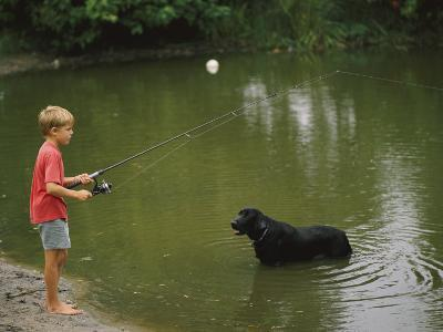 Boy Fishing in a Pond with a Black Labrador Retriever Standing in the Water-Brian Gordon Green-Photographic Print