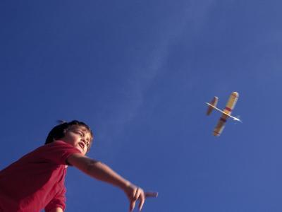 Boy Flying Toy Airplane-Kevin Leigh-Photographic Print