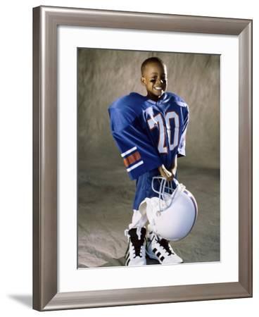 Boy in an Oversized Football Uniform Holding a Helmet--Framed Photographic Print