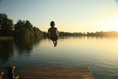 Boy Jumping into a Lake from a Dock at Sunset in the Summer-David Polite-Photographic Print