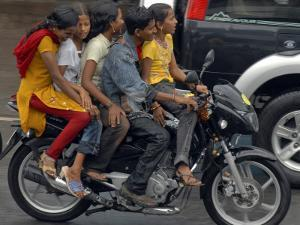 Boy Rides a Motorbike with Four Girls, as it Drizzles in Hyderabad, India