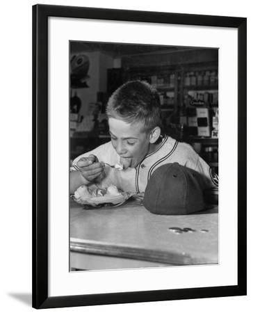 Boy Wearing Baseball Uniform Eating Banana Split at Soda Fountain Counter-Joe Scherschel-Framed Photographic Print
