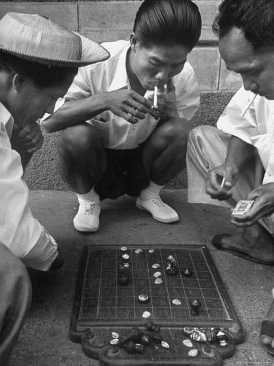 Boys Playing Board Game on Sidewalk in Front of the Trocadero Hotel-Dmitri Kessel-Photographic Print