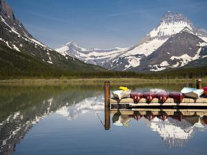 Colorful Canoes Line the Dock at Many Glacier Lodge on Swiftcurrent Lake During Sunrise by Brad Beck