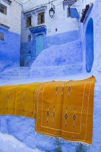 Africa, Morocco, Chefchaouen. Rugs Draped on a Wall in the Blue Town by Brenda Tharp