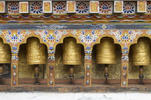 Bhutan. Spinning prayer wheels along a temple wall. by Brenda Tharp