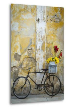 Cuba, Havana. Bicycle with Flowers Leaning Against a Decaying Wall
