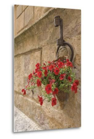 Italy, Tuscany, Pienza. Colorful Petunias Spill from a Basket on a Stone Wall