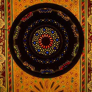 Morocco. A graphic silhouetted detail of a metal Moroccan lamp in a ceiling of a restaurant. by Brenda Tharp