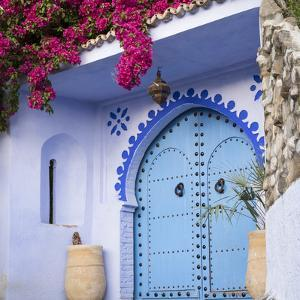 Morocco, Chefchaouen. Bougainvillea Blossoms Frame an Ornate Blue Door by Brenda Tharp