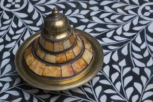 Morocco, Fes. A covered brass bowl with inlay of camel bone sites on a stone inlay table in a shop. by Brenda Tharp