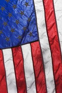 Sunlight shines through an American Flag. by Brenda Tharp