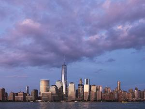 Sunset reflects off the buildings of lower Manhattan, seen from the water, New York City, New York. by Brenda Tharp