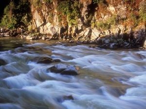 The Payette River Flows by with Lit Rock Wall Behind, Idaho, USA by Brent Bergherm