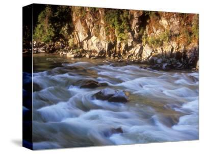 The Payette River Flows by with Lit Rock Wall Behind, Idaho, USA
