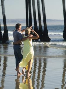 Couple on Beach Below Pier, Pismo Beach, California by Brent Winebrenner