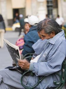 Man Reading Newspaper, Plaza de Armas, Peru by Brent Winebrenner