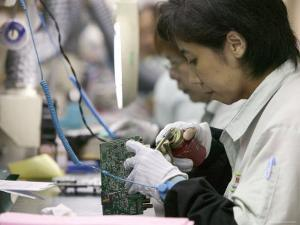 Woman Assembling Computer Boards, Taipei, Taiwan by Brent Winebrenner