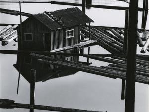 Logs, Building, Water, 1982 by Brett Weston