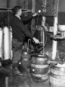 'Brewmeister' Fills Kegs at a Bootleg Brewery During Prohibition, 1933