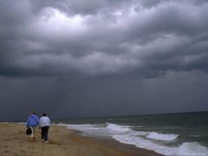 Daughter and Mother Walk Along a Beach, Storm Clouds Darken the Sky by Brian Gordon Green