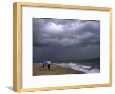 Daughter and Mother Walk Along a Beach, Storm Clouds Darken the Sky