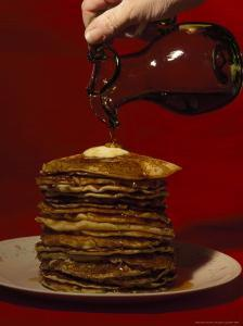 Hand Pours Syrup onto a Stack of Pancakes by Brian Gordon Green