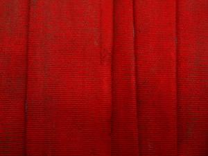 Bright Red Fire Hose Made of Tightly Woven Fabric and Folded into Layers