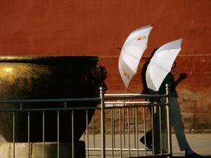 Two Young Women with Umbrellas Standing Beside Water Urn, Forbidden City, Beijing, China by Bruce Yuan-yue Bi