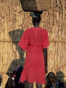 Back View of a Nuer Woman Carrying a Wicker Cradle or Crib on Her Head, Ilubador State, Ethiopia by Bruno Barbier